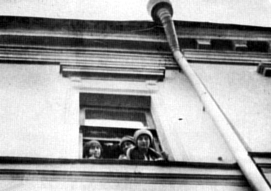Grand Duchesses Anastasia, Marie, and Tatiana looking out a window of the Governor's mansion in Tobolsk, Siberia during captivity.