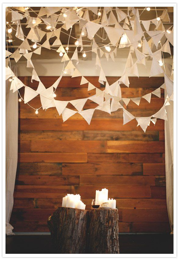 Creamy flag bunting is intertwined with bistro lights on the ceiling while rustic logs and candles create a balanced glow on the floor level. Source