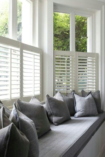 Half height shutters behind a window seat.