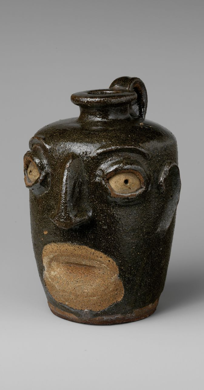 John Lewis Miles Pottery - Face Jug, ca. 1860–70 / Face jugs were made by African American slaves and freedmen working in potteries in the Edgefield District of South Carolina, an area of significant stoneware production in the nineteenth century. The distinctive features of the jugs, notably the kaolin inserts for the eyes, relate in style and material to ritualistic objects of the Congo and Angola region of western Africa, whence many slaves in South Carolina descended.