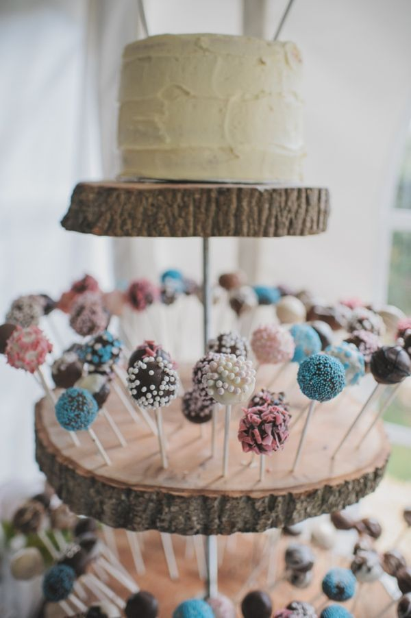 Colorful and rustic cake pop display with a layer of cake on top #wedding #rustic #cakepops #weddingdessert #desserttable
