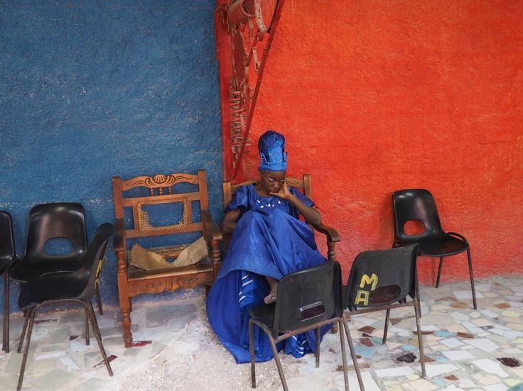 Picture of woman in a blue dress, resting.  A performer takes a break from playing music in one of Havana's art districts, a street called Callejón de Hamel, where musicians and artists gather to display their work.  PHOTOGRAPH BY JONATHAN LÓPEZ ÁVILA
