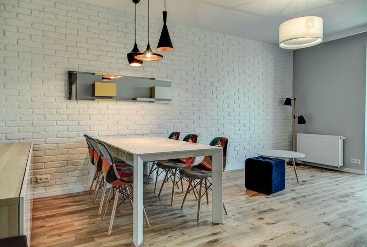 Aranżacja jadalni w salonie. Białe wnętrze gdzie uwagę przykuwają kolorowe dodatki, jak np. patchworkowe obicia kompletu krzeseł. Stół jadalniany posiada oddzielne oświetlenie w postaci trzech lamp w stylu Toma Dixona.