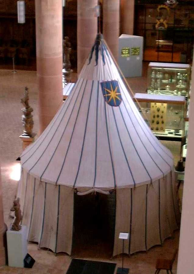 """pre-1655 Tent in Basel museum. """"It is NOT a hub and spoke design.  It is supported by a single pole and   intended to be held out by the ropes (in a crow's foot fashion).  In the museum it has an internal structure which they use for displays inside the pavilion and convenience of not having to have the ropes spread out in the museum.   The walls are attached (stitched) to the roof   The colored lines are stitched on.  On the roof, the blue canvas is stitched over every seam. """""""