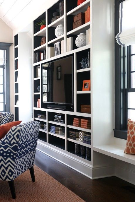 Blue and orange living room features a floor to ceiling built in media unit, with backs of shelves painted blue, filled with a flatscreen TV and orange accents placed next to a floating window seat under a blue framed window.