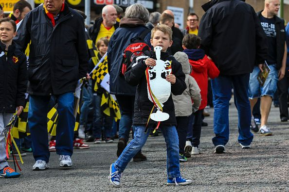 News Photo : A Watford fan leans into the road, clutching a...