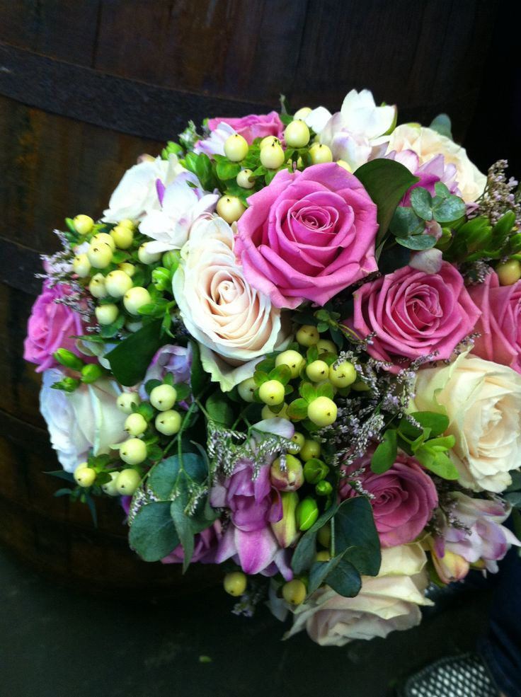 A mix of roses, limonium, hypericum berries, and a selection of greenery.