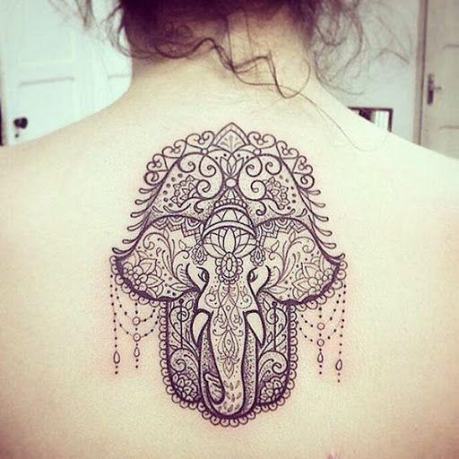 Um elefante é embelezado com uma mandala padrão e suspensão de contas em preto tatuagem prestados no meio do utente na parte superior das costas.