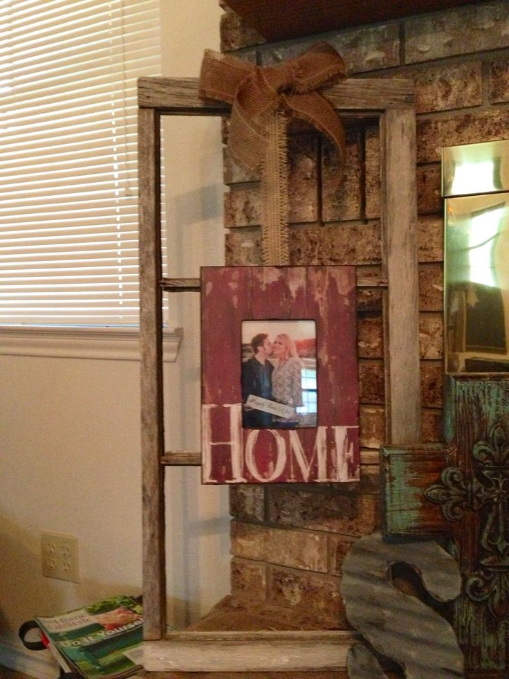 Old window frame with new picture tied with burlap.