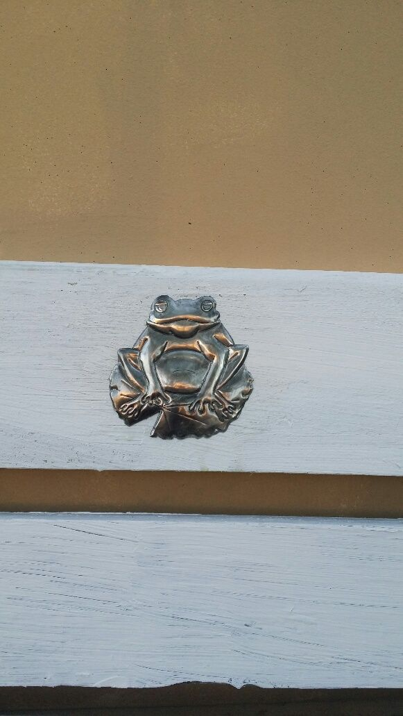 pewtered frog on garden bench