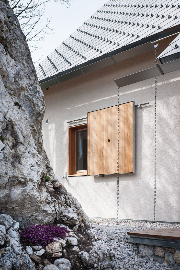 The roof is covered in thin, overlapping fibre-cement tiles laid to create a cross-hatched pattern, while galvanised metal accents update traditional wooden elements like window shutters and frames.