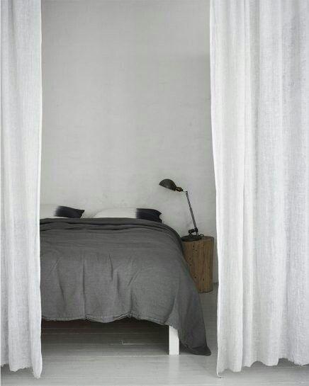 Grijze muur met witte linnen gordijnen