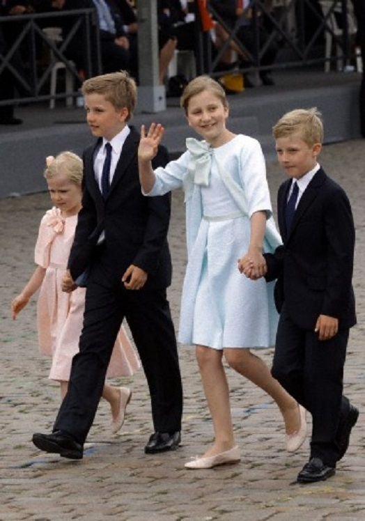 Belgium's Crown Princess Elisabeth waves to the crowd as she walks with her brothers Prince Gabriel, second left, and Prince Emmanuel, right, and her sister Princess Eleonore, left, during a military parade on Belgian National Day, in front of the Royal Palace in Brussels, 21.07.2014.