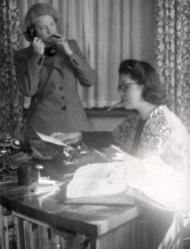 Het roken van sigaren, rokende vrouwen: Twee vrouwen roken een sigaar. De één tijdens het telefoneren, de ander terwijl ze met papieren bezig is.1941.