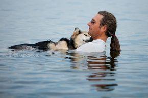 Homem conforta velho cão que salvou sua vida. (Quando John Unger pensou cometer suicídio depois de uma separação, foi sua cadela Shoep que o trouxe de volta da beira do abismo. Esta fotografia mostra Unger embalando seu amigo no Lago Superior para aliviar a artrite do cão.)
