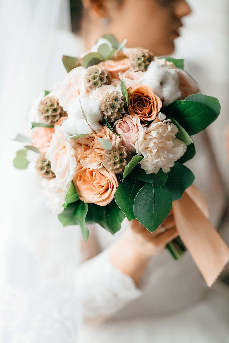 elegant bridal bouquet In a gentle peach color with the use of tender carnations, cotton and peach roses