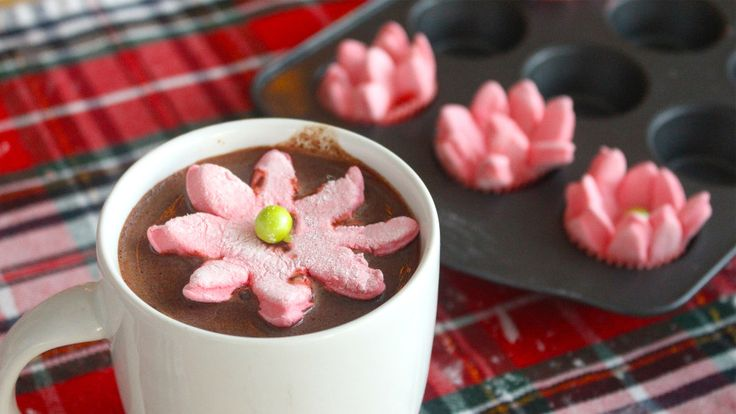Recipe with video instructions: Pop these marshmallows into your hot chocolate and watch them bloom into poinsettias! Ingredients: 2 ½ tsp powdered gelatin, 1/3 cup cold water, 1 cup sugar, ¼ cup cold water, red food colouring, ¼ cup corn starch, ¼ cup confectioner's sugar, Red candy melts, Round candies