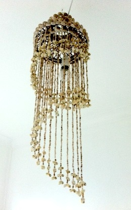 This light is made out of hundreds of tiny shells.  It certainly adds a touch of uniqueness to this goregous bedroom space.