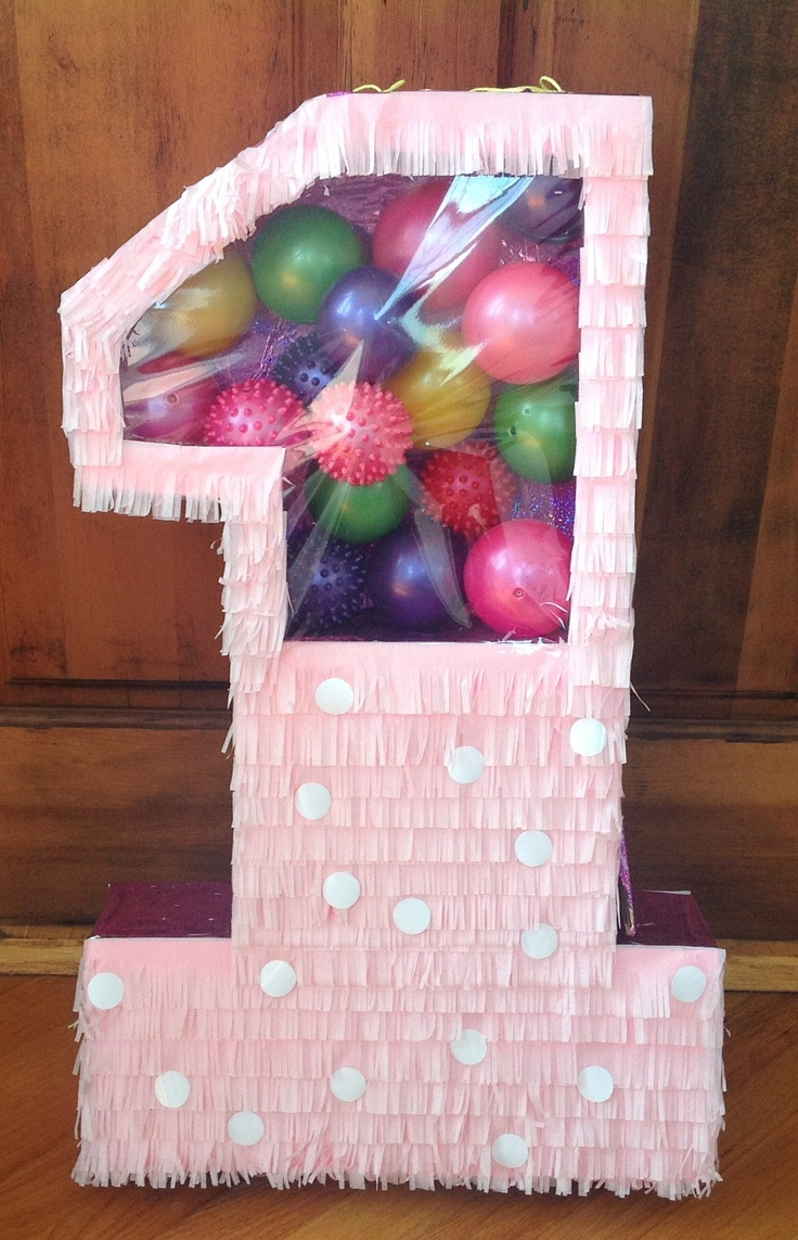 Number one piñata , pink with white dots.  Top section filled with balls, bottom section with candy.