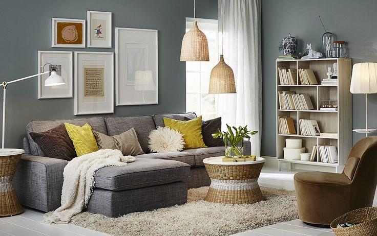Salón con un sofá gris de dos plazas con chaise longue, una mesa con bandeja redonda y un sillón giratorio cubierto con un terciopelo de color beige oscuro.