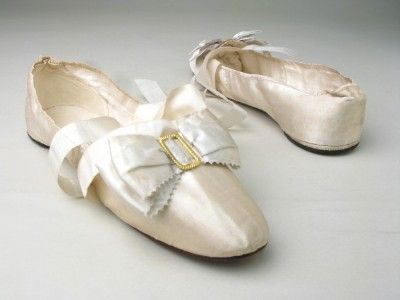 Manchester City Galleries item 1956.298,  1800-15, White satin over white linen, bound with white silk ribbon. Leather soles, kid insoles.    Rounded toes, square fronts (vamp throat). White silk ribbon ties each side. Fronts trimmed with white satin ribbon bow with small gilt metal buckle. Very low heels.