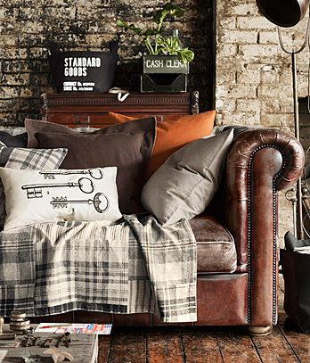 old leather couch, various pillow cases