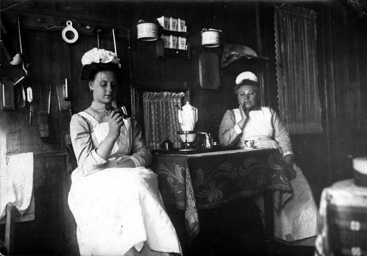 Dienstpersoneel, Nederland, 1912. Amsterdamse dienstmeisjes (dienstbodes, huishoudsters) drinken koffie. De linker met een moderne Engelse flodddermuts, de rechter met echte Amsterdamse tulenmuts.