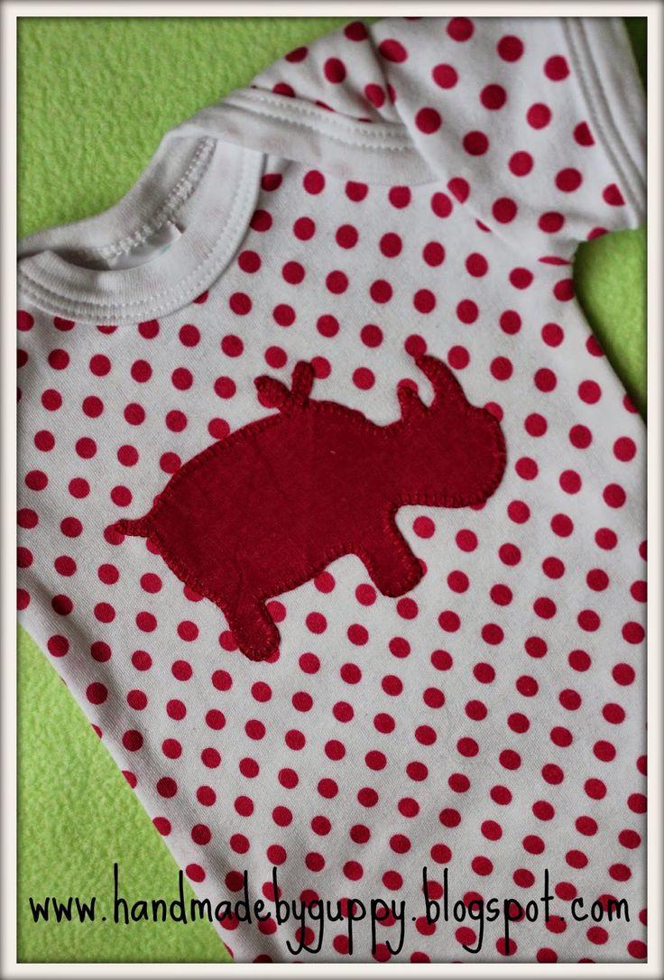 Handmade by Guppy. Bright pink rhino on pink polka dot onesie