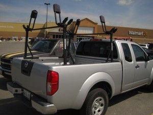 """Image of a Nissan Frontier 2 Door bed mount rack system for kayaks using the Outdoorsman 300 Compact truck rack with LB58 58"""" cross bars and two Yakima HullRaiser kayak J-cradles."""