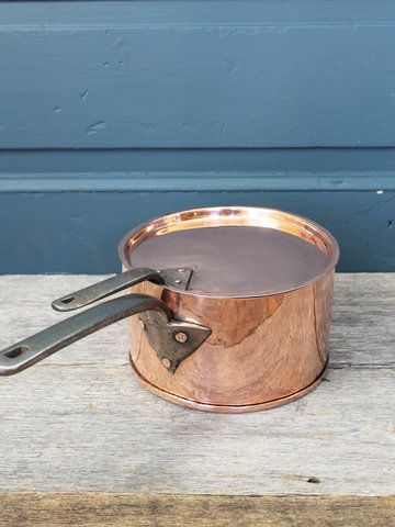 A traditional Saucepan from England that features all handmade details. Heavy iron handles to both the lid and pot secured by hand rolled copper rivets. This pot also has dovetailed seams down the back with a brazed bottom. This piece has been restored for use. C. 1850