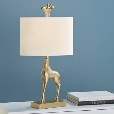 Quirky becomes well curated when it's an extension of your so-chic-but-unexpected design personality. It's the reason to love our Giraffe Table Lamp. Gold tones are still getting big love for home accents, along with organic patterns and globally inspired pieces, and this fellow checks the box for all three. Over 2 ft. tall, with a uniquely oval, hardback fabric shade, he is an elegant beast. Table lamp fashioned like a gold-toned giraffe ...