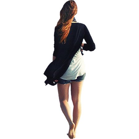 A PNG file with background removed of a young woman in shorts walking along the beach.