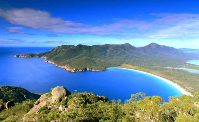 "Wineglass Bay, Australia: Located in Tasmania, this beach often shows up on ""world's most beautiful"" lists—but its past is not so picture-perfect. In the 1820s, whalers descended on the bay, sparking conflict with the native Pydairrerme aboriginal tribe. The bay's name comes from all of the whale blood that would stain the bay dark red when the whalers were working.  (timphillipsphotos/Getty)"