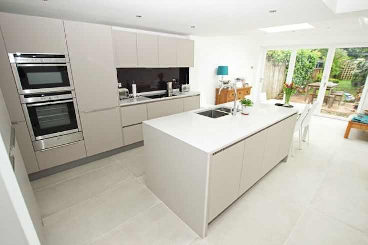 Modern kitchen extension with kitchen island.  The kitchen has matt cashmere handleless kitchen doors and is finished with a deep and luxurious purple splashback.