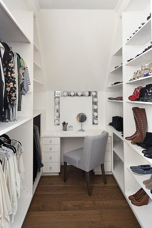 Stacked clothing rails facing white built in modular shoe and boot shelves flank a white lacquered makeup vanity seating a gray wingback vanity chair in front of a vanity mirror lit by Hollywood lights.