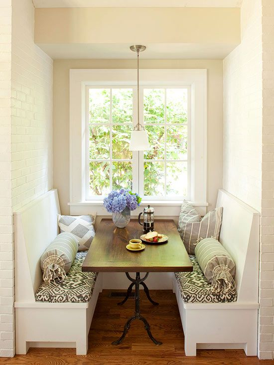 Symmetrical Space  A pair of built-in benches and a narrow dining table create an elegant look in this small breakfast nook. Boldly patterned seat cushions add visual weight to the all-white nook and adjoining kitchen. A dainty light fixture overhead boosts visibility after the sun goes down without overwhelming the tiny space.