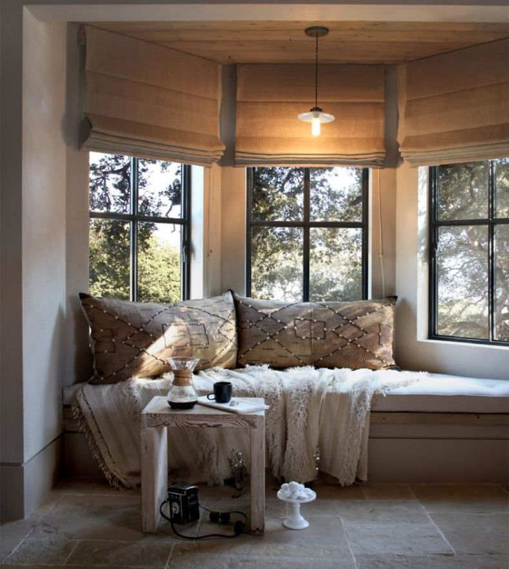 Un banco junto a la ventana, un lugar ideal para descansar, leer o simplemente pensar. Los tonos ocres crean un espacio confortable y cálido.
