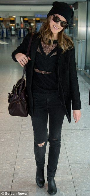 Emma Watson wore a black top with sheer panels, ripped jeans and quirky Chelsea boots