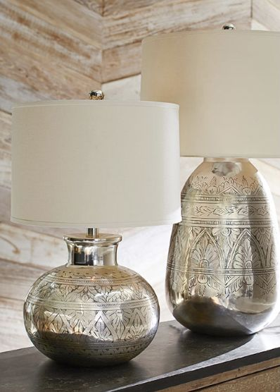 The antique-silver finish on this lighting is applied by hand to reveal the finely etched floral patterns. Our lamp base brings shine and global chic to a room.                                                                                                                                                                                 More