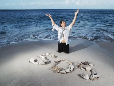 How Did SOS Become the Universal Distress Signal?: Ragged businessman on beach with 'S.O.S.' made from rocks and shells