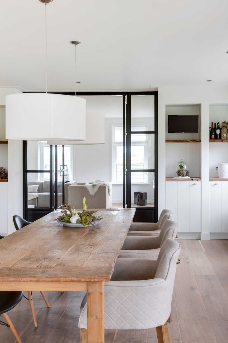 Modern dining room with a large wooden dining room, light grey chairs, a white pendant light and a black-framed door.