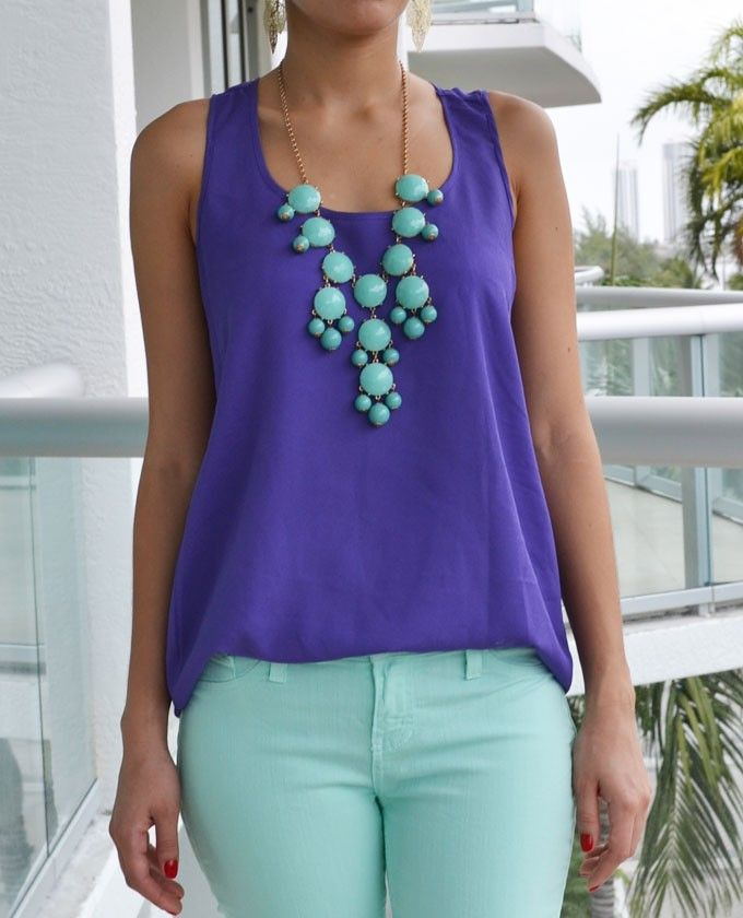 "The right pop of color for a basic tank top featuring a scoop neckline and asymmetrical hem. Racer back and relax fit. Perfect to pair with jeans and/or to create a color block outfit. Small measures 24.5"" from shoulder to hem. 100% Polyester. Hand Wash Cold. Imported. $28.00"