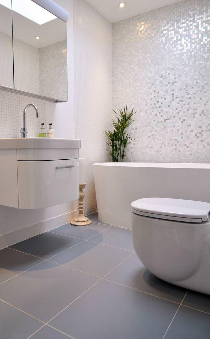 Design bagno contemporaneo moderno con la parete dietro la vasca rivestita in mosaico bianco con riflessi metallici