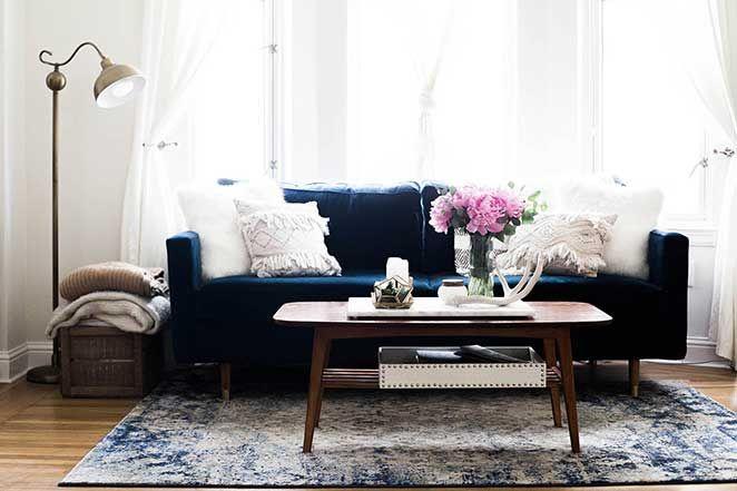 O sofá em azul marinho tomou conta do recado e se tornou um chamariz irresistível para quem a visita. Para equilibrar, o restante da decoração ficou por conta de tons claros, como branco, bege e amadeirado.