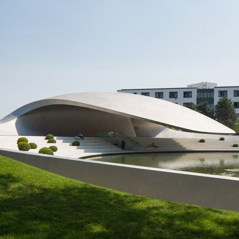 German architects HENN have created a streamlined pavilion with a curled-over steel roof for car brand Porsche at the Autostadt theme park in Wolfsburg.