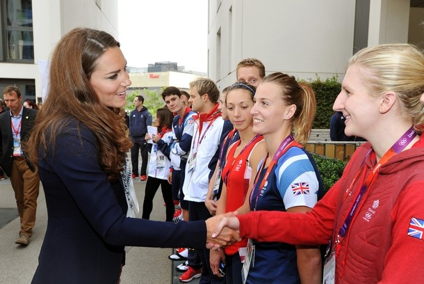 Catherine, Duchess of Cambridge, shakes hands with Great Britain swimmer Rebecca Adlington (R) during a visit to team GB accommodation flats in the Athletes Village at the Olympic Park in Stratford, east London, on July 31, 2012.