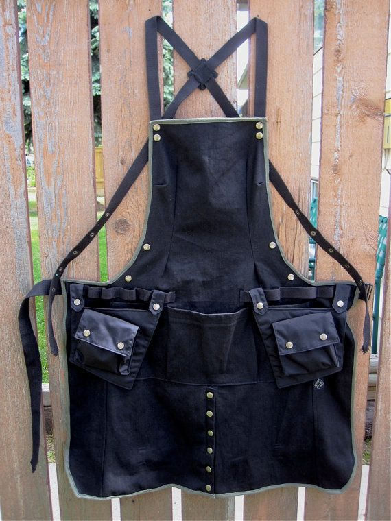 Multi functional black canvas cargo apron, with leg split, and optional leg straps to keep legs covered to knee length. Has adjustable crossing