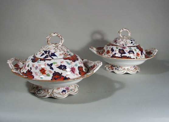 A Pair of Coalport Porcelain Covered Vegetable Tureens, Circa 1830 The pair of serving dishes is beautifully decorated with an orange-ground and floral motif loosely based on the Imari palette with underglaze cobalt painting, polychrome enamels and gilt accents, all on moulded and scalloped footed base; flanked by moulded handles in the form of acanthus and topped by a moulded acanthus-leaf handle.