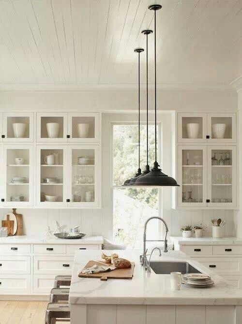 White kitchen cabinets with glass doors, white marble countertops, wood floors