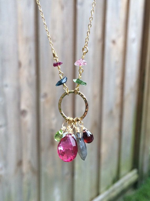 This listing is for one beautiful, multi-gemstone necklace. I have used cool pink, green, and red stones that look amazing and summery. This design is unique and versatile, and full of gorgeous gems! - > Gemstones include peridot, moonstone, berry quartz, labradorite, and garnet. The gems hang from a small hammered silver ring. - > Wire wrapped tourmaline gemstone chips connect from the chain. - > The chain is gold filled and measures 20. Necklace is finished with a spring ring clasp…